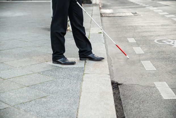 Man stepping off a pavement with a white cane