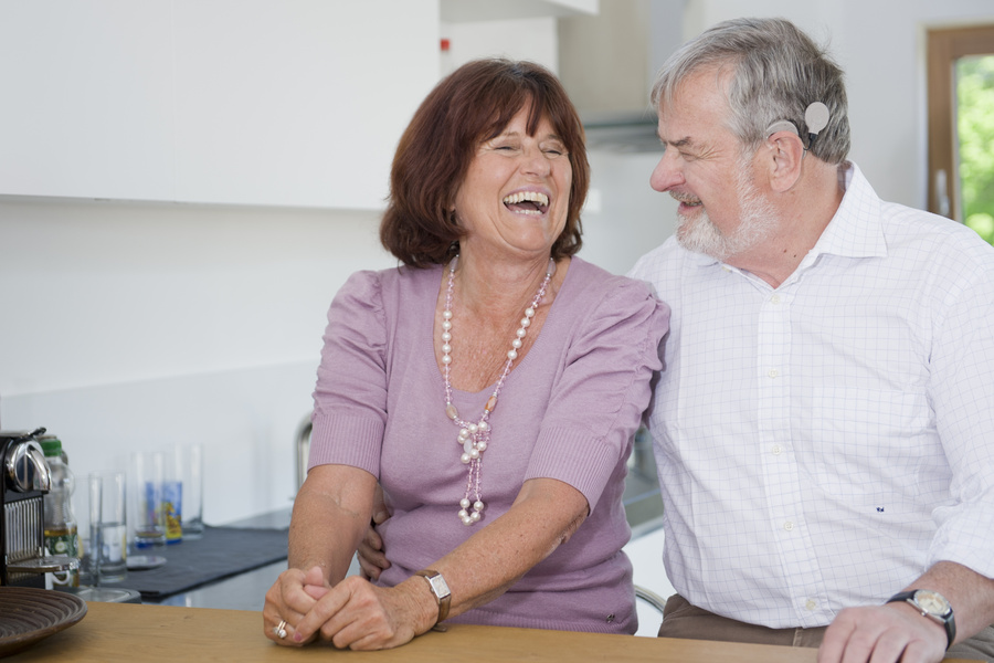 Man with a cochlear implant laughs with his wife