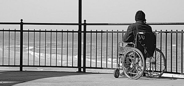 Young man in a wheelchair looks over railings towrds the sea