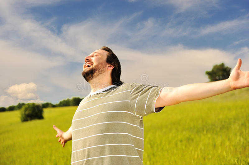 Happy man in a field with arms open wide
