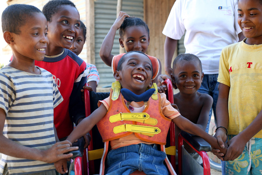 Young boys around a bow in a wheelchair, laughing