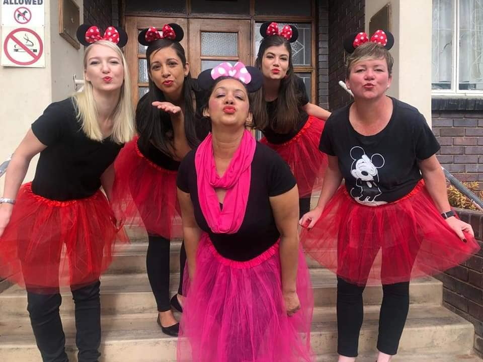Group of ladies dressed in black with pink/red net tutu skirts, Minnie ears and posing for the cameraears and